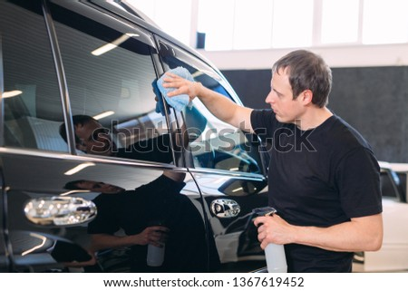 The man is wiping with a cloth body of a brilliant car. #1367619452