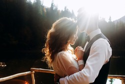The man kisses the bride on the forehead in the sun