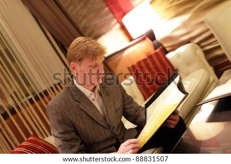 The man looking at a menu in hotel restaurant