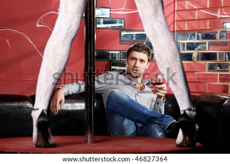 The man looks at a striptease in club
