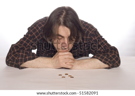 The man looks at coins in meditation.