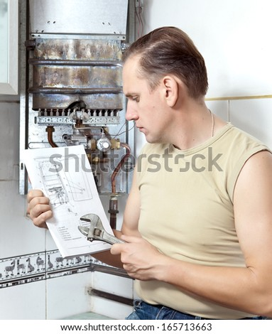 The man looks the instruction on repair a gas water heater.