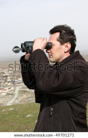 The man looks through a binoculars, Kyrgyzstan - stock photo
