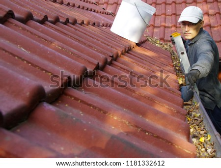 The man on ladder cleans the gutters on the roof. Spring and autumn problem with leaves in gutter. #1181332612