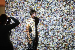 The man on the background of the projection of colored pixels. Pixels are chaotic in shape and color. The man on the background of the projection of colored pixels