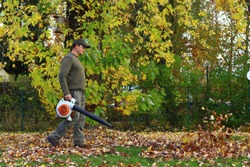 The man operating the leaf blower. Autumn work.