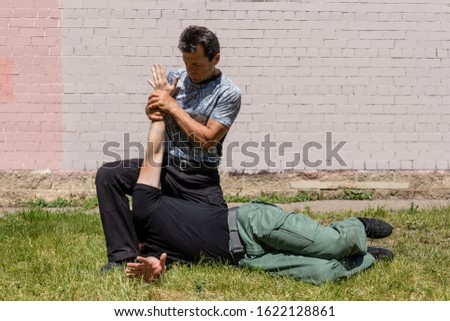The man performes a painful fixation technique. Martial arts instructors demonstrate self-defense techniques of Krav Maga