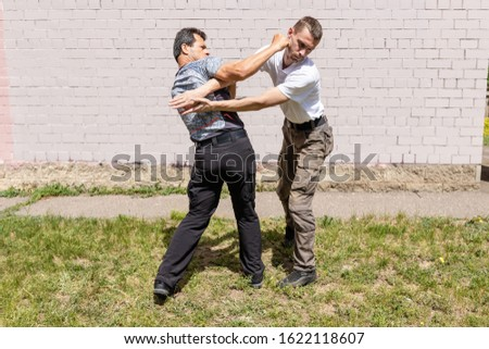 The man performs the reception from the capture, while striking the attacker. Martial arts instructors demonstrate self-defense techniques of Krav Maga