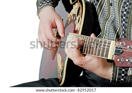 The man plays an electric guitar close-up