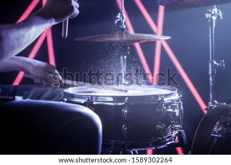 the man plays the drums, the game is on the working drum with sticks close-up. On the background of colored lights with splashes of water. Musical concept with a working drum.