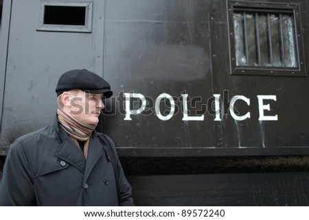 The man posing on the police carriage background