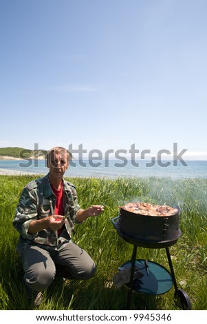 The man prepares for a barbecue on seacoast