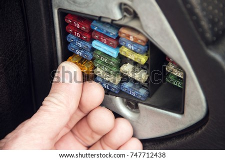 The man presses his finger on the electric fuse in the car to insert it into place.