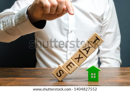 The man pushes down the tower of cubes with the word Taxes on the figure of the house. Heavy tax burden, lack of liquidity of assets and real estate. Tax breaks, relief, loopholes in laws. Declaration Stock photo ©