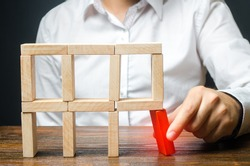 The man removes the red structural element, which will collapse. Incompetent businessman. Loss of key elements and employees. Damage to the opponent. Destruction of a complex structure by negligence.