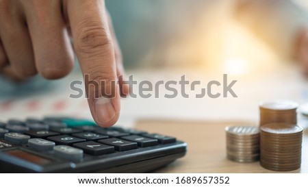 The man's finger that presses the calculator to calculate and analyze income and expenses the growth of coins and financial costs, wisely and prudently, the concept of investment ,savings and debt