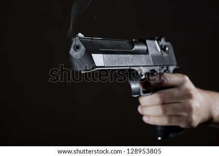 The man's hand holds a pistol, from a trunk there is a smoke
