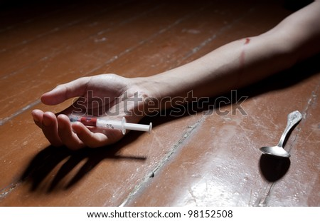 The man's hand lies on a floor, the syringe, a spoon nearby lie - stock photo