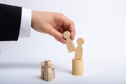 The man's hand of a businessman in a business suit holds a wooden figure of a man in his hand and moves another figure from his post. The concept of firing an employee, the replacement of staff