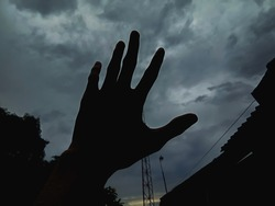 the man's hand that raised to the cloudy sky on a dark afternoon