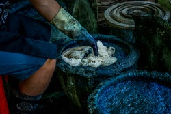 The man's hands are dipping the cloth into a dyed indigo tank. The jar of indigo dyed. Indigo is made from natural ingredients. Indigo Dye in Thailand.