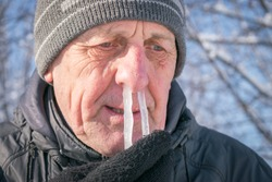 The man's snot was frozen in his nose. Portrait of an elderly man with icicles in his nose. Runny nose in the winter forest. Frosty weather in winter. Comic concept of a winter cold.