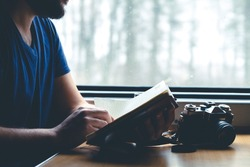 The man sits at a table in a train, looking into the notebook