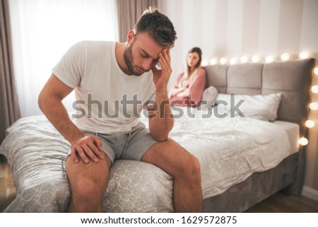 The man sits at the end of the bed and holds his head after the fight he had with his girlfriend as she lies on the bed next to him.