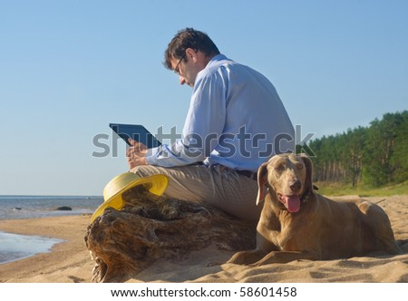 The man sits on seacoast with a dog and the computer