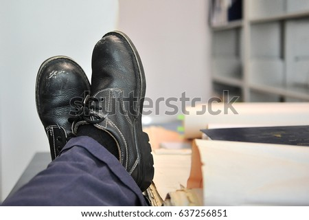 The man sitting in the office with his feet resting on the table  and the shoes is old style. #637256851