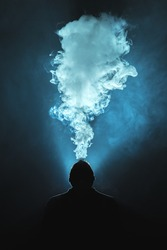 The man smoke an electronic cigarette against the background of the bright light