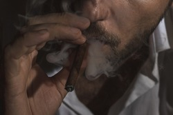 The man smoking a small cigar, cigarillo. The adult man, 34 years old, is smoking cigarillo and blows smoke out of the mouth. Close-up photography of smoking cigar.