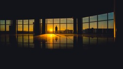 The man stand by the window on the sunset (sunrise) background