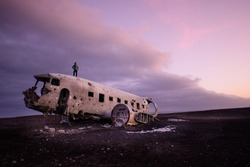 the man stand on the  abandoned DC Plane on Sólheimasandur in Iceland as one of the tourist destination