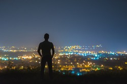 The man stand on the background of the city lights. night time