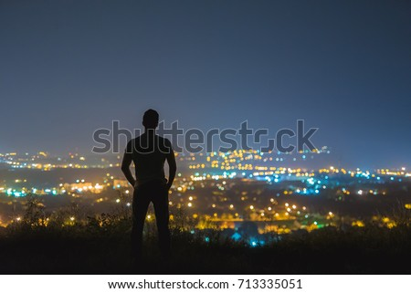 The man stand on the background of the city lights. night time  #713335051