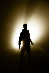 The man standing alone silhouette the darkness, abstract mysterious sci fi fantasy concept, bright light rays from behind, person alone in dark background