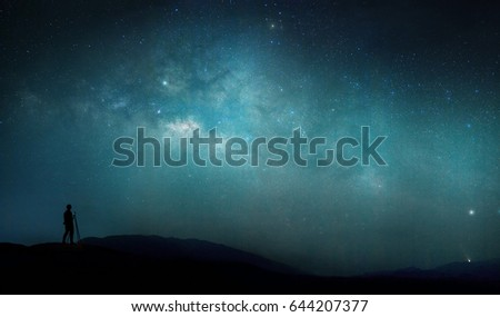 The man standing on the mountain cliff at night looking full stars on sky with beautiful light of milky way galaxy. panorama shot