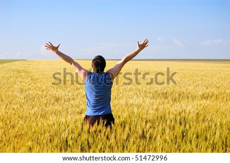 The man stands a back in an autumn field. Has lifted hands upwards