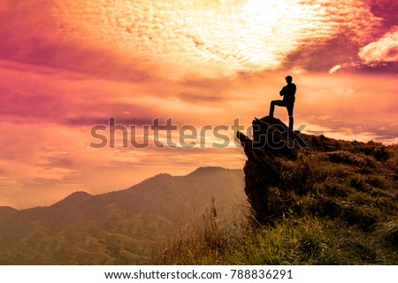 The man stands on a cliff top and orange  Purple sky