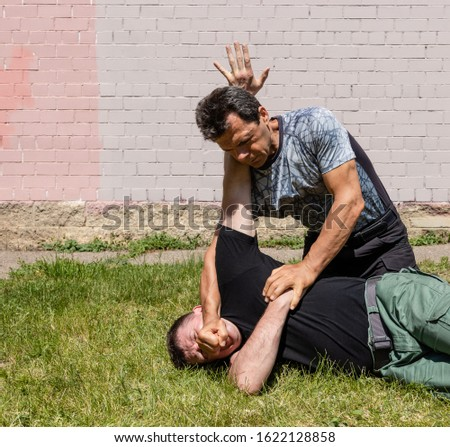 The man strikes back to the attacker with his fist. At the same time, he performed a painful fixation technique. Martial arts instructors demonstrate self-defense techniques of Krav Maga