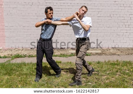 The man strikes back with the fist in the jaw of the aggressor, while fixing the attacker`s hand. Martial arts instructors demonstrate self-defense techniques of Krav Maga