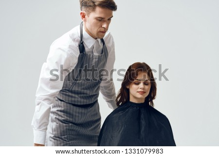 The man the hairdresser in an apron does a hairdress to the woman a beauty salon