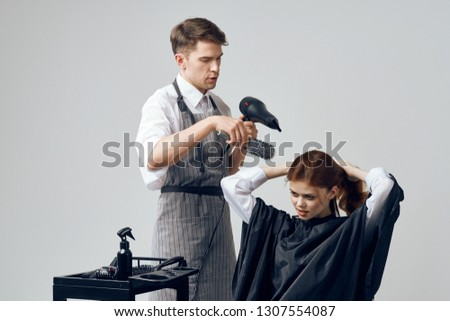 The man the hairdresser in hands does a hairdress to the woman on a gray background