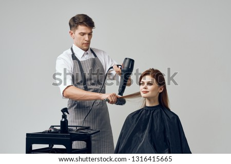 The man the hairdresser with the hair dryer in hands does the woman a hairdress a gray background
