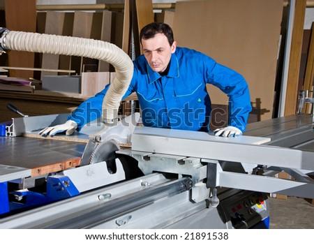 The man the worker, works on the machine tool and saws wooden products