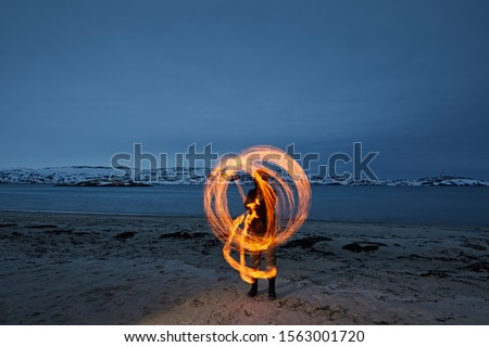 The man turns poi with fire, forming a track in the form of a circle. Action prohodi on the sandy beach against the blue night sky.