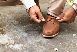 The Man tying shoelaces on classic brown shoes