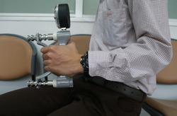 The man using grip strength dynamometer for testing hand grip strength. Testing hand grip strength. Hand grip strength evaluation for health indicator