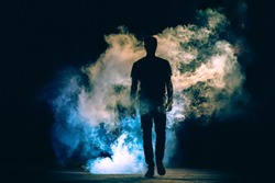 The man walking in the smoke on the dark background. evening night time